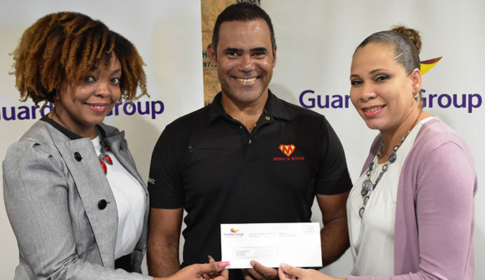 Michael Phillips (centre) of Phillips Promotions receives a cheque from Ayesha Boucaud-Claxton (right), Senior Manager, Group Corporate Communications and Kele Ransome, Corporate Communication Officer- CSR & Event of Guardian Group.